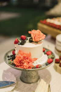A cake decorated with fruit and flowers from Off the Beaten Path Weddings